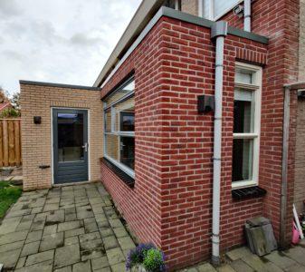 Uitbouw van een woning met nieuwe bijkeuken en extra ruimte.